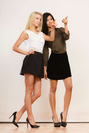 skirts: Two young women caucasian and mixed race in trendy short black skirts posing in full length pointing into the copyspace, studio portrait