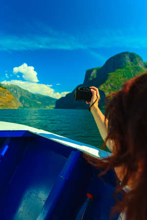 sognefjord: Tourism vacation and travel. Woman tourist taking photo with camera, view from deck of ship on fjord Sognefjord in Norway, Scandinavia.