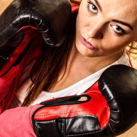 emancipation: Emancipation and feminist. Defense concept. Young fit woman boxing. Indoor. Stock Photo