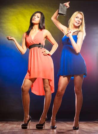feminismo: Feminismo y emacipation. Partido, celabration, carnaval. Dos mujeres atractivas en vestidos de baile en el fondo colorido en estudio.