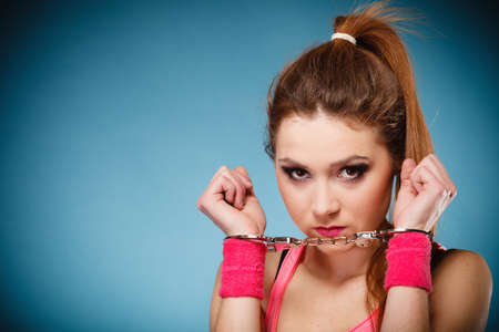 Teen crime, arrest and jail - Criminal teenager girl prisoner woman in handcuffs blue background photo