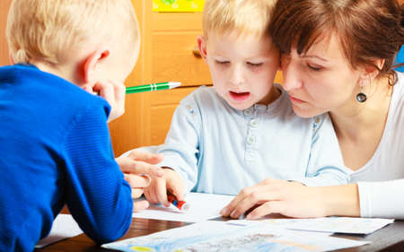 daycare: Family, children and happy people concept. Mother and sons drawing together, mom helping with homework Stock Photo