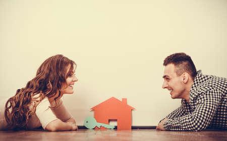 bienes raíces, familia y pareja concepto - sonriente pareja acostado en el piso con la casa símbolo y soñar despierto clave en el hogar, filtro de la vendimia