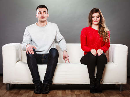 Shy woman and man. Guy sitting near attractive young woman on sofa and making hand gesture walking with finger to girl Stock Photo
