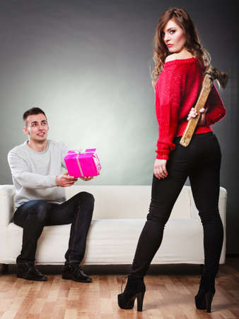 trusting: False feelings, relations problem. Trusting guy giving present pink box to misleading girl. Insincere woman holding axe behind her back Stock Photo
