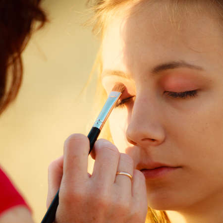 makeover: Cosmetic beauty procedures and makeover concept. Makeup artist applying with brush color eyeshadow on female eye.