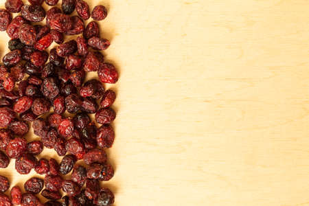 cranberry fruit: Healthy food organic nutrition. Border frame of dried cranberries cranberry fruit on wooden background