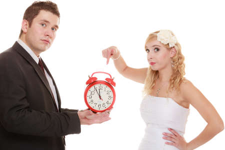 undecided: Wedding concept. Time to get married. Unhappy undecided bride and groom with red alarm clock making decision or to be late isolated on white Stock Photo