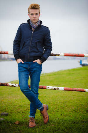 denim jacket: Autumn fashion. Young handsome man model in full length casual style hair styling outdoor against overcast sky, cold autumnal foggy day