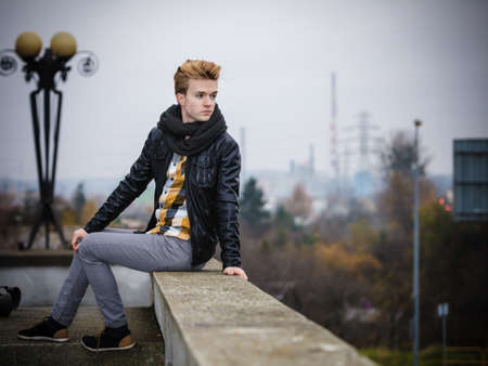 cityspace: Street fashion. Young fashionable man guy with stylish hair posing outdoor on cityspace background