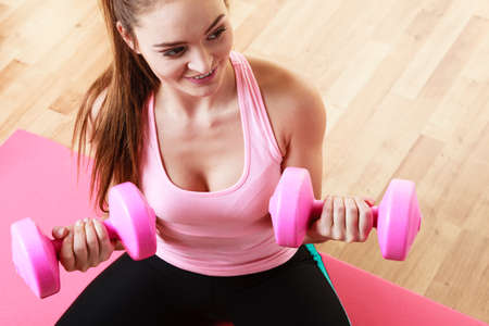 dumb: Fitness girl fit woman with dumbbells, doing exercise with dumb bells training with weights at home