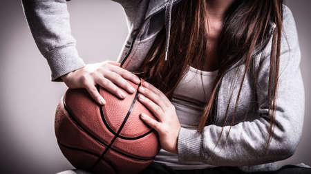 Pelo largo chica adolescente mujer deportiva joven celebración de baloncesto en el fondo gris