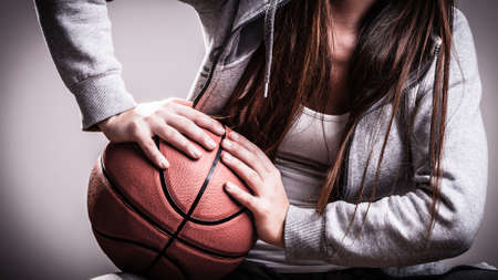 basketball: Young sporty woman teen girl long hair holding basketball on gray background