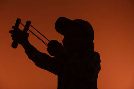 naughty boy: Children upbringing problems. Kid holding slingshot in hands. Bad naughty boy silhouette shoots from a wooden sling on orange background