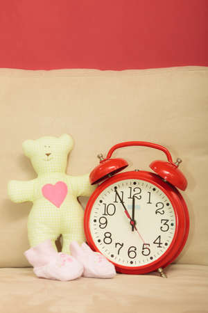 Are You Ready - pregnancy concept. Cute teddy bear toy, small shoes for unborn baby and red alarm clock on sofa at home photo