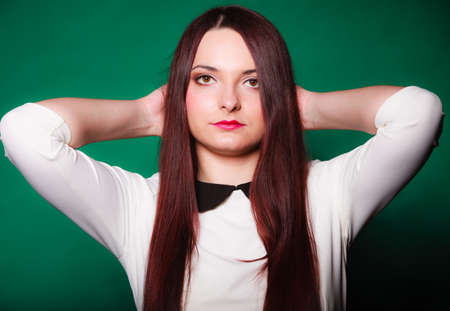 bussines people: Attractive women. Lifestyle concept. Young woman straight long dark hair posing in studio on green background.