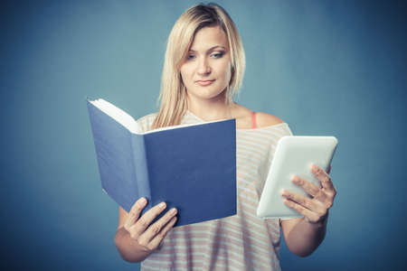 ebook: Ebook vs book. Young woman using tablet computer reading. Female with traditional book and e-book reader touchpad pc blue background. Vintage filter