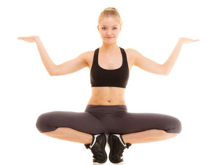 Sport and active lifestyle. Full length of fitness sporty girl stretching showing open hands palm with blank copy space for product or text isolated.