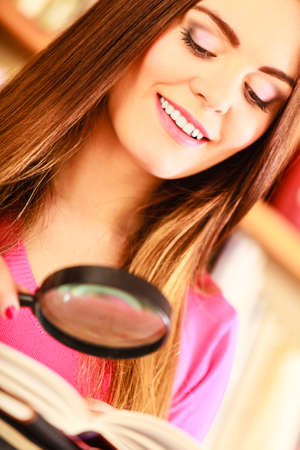 lupa: Investigation exploration education concept. Closeup intelligent student girl in library, woman holding magnifying glass loupe