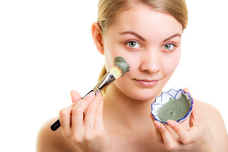 Skin care. Woman applying with brush clay mud mask on face isolated. Girl taking care of dry complexion. Beauty treatment. Stock fotó