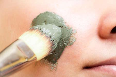 Protección de la piel. Primer de la mujer de la aplicación con la arcilla cepillo máscara de barro en la cara. Muchacha que toma el cuidado del cutis seco. Tratamientos de belleza.