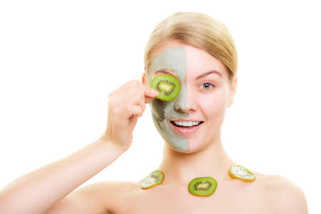 purifying: Skin care. Woman in clay mud mask on face and necklace with slices of kiwi fruit covering eye isolated. Girl taking care of dry complexion. Stock Photo