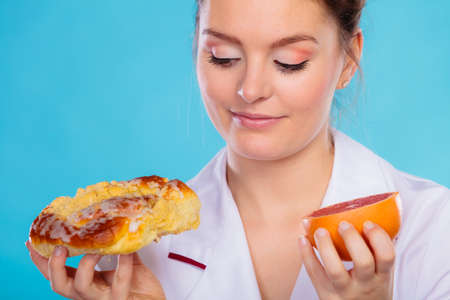 bad diet: Make the right dietary choice concept. Nutritionist comparing diets options, holding cake sweet food and grapefruit on blue