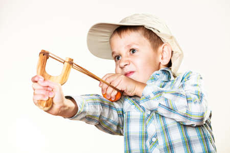 Children upbringing problems. Kid holding slingshot in hands. Bad naughty boy shoots from a wooden sling on white