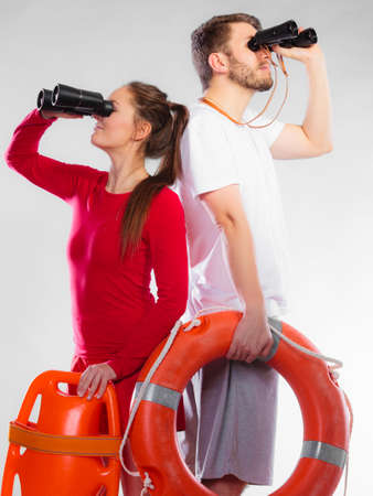 observant: Accident prevention and water rescue. Young man and woman lifeguards on duty looking through binoculars keeping buoy lifesaver equipment on gray Stock Photo