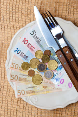 Cost of living, price of food and eating wealth concept. Euro money on kitchen table, plate with cutlery photo