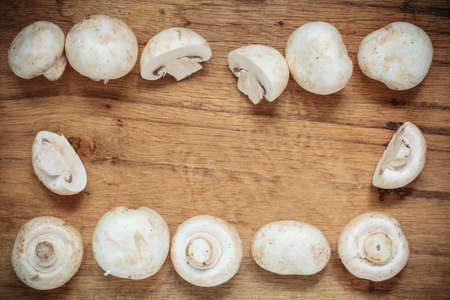 fungoid: Vegetarian food. Frame of fresh white mushrooms champigonons on wooden kitchen table background.