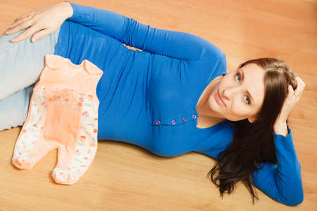 unborn: Pregnancy, motherhood and happiness concept. Pregnant woman lying on floor with clothes for the unborn baby, getting ready for the babys arrival