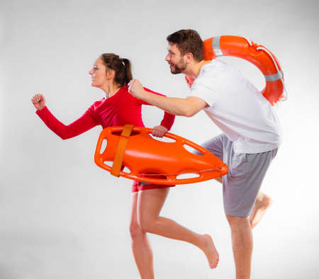 duty belt: Accident prevention and water rescue. man and woman lifeguard couple on duty running with with life belt lifesaver equipment on gray
