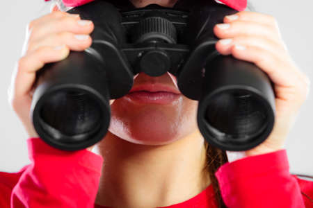 observant: Accident prevention and water rescue. Closeup girl in red lifeguard outfit on duty looking through binocular on gray Stock Photo