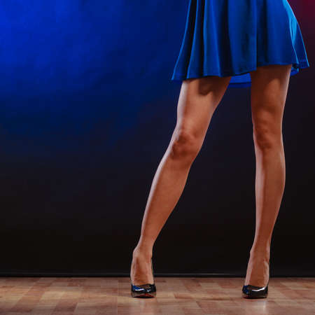 New year, celebration, disco concept - woman in evening dress dancing in the club, part of body female legs in high heels on party floor photo