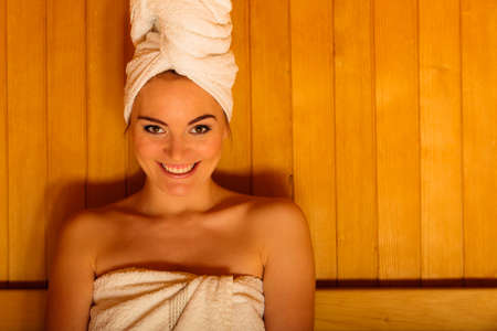 Spa beauty treatment and lifestyle relaxation concept. woman white towel relaxing in wooden sauna room. Stock Photo