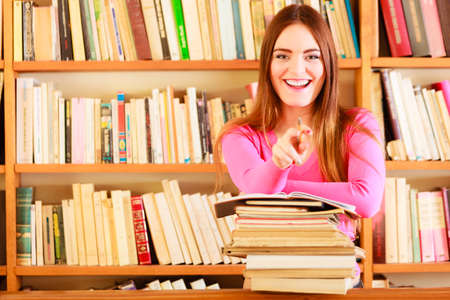 encyclopedia: Education school concept. Happy female student fashion long hair girl in college library with stack books making research pointing with pen