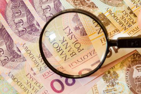 Counterfeit money concept. Polish zloty banknotes currency and magnifying glass Stock Photo