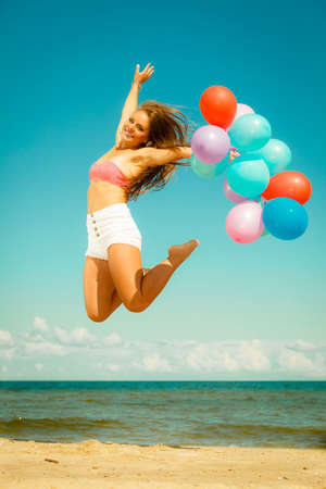 Summer holidays, celebration and lifestyle concept - beautiful woman teen girl jumping with colorful balloons outside on beach photo