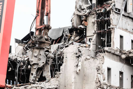 deconstruction: Urban scene. Dismantling of a house. Building demolition and crashing by machinery for new construction. Industry. Stock Photo