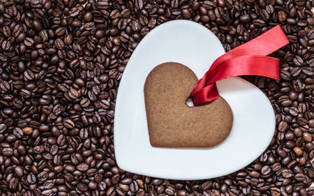 robbon: Coffee time concept. Heart shaped plate and cookie gingerbread with red robbon on coffee beans background. Top view