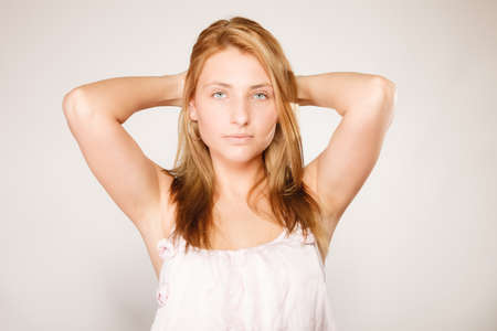 tratment: Skin care. Attractive blonde woman with no makeup, fresh face with natural make up on gray