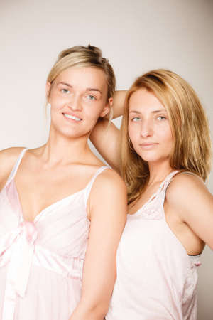 tratment: Attractive two blonde women with no makeup, fresh face with natural make up on gray
