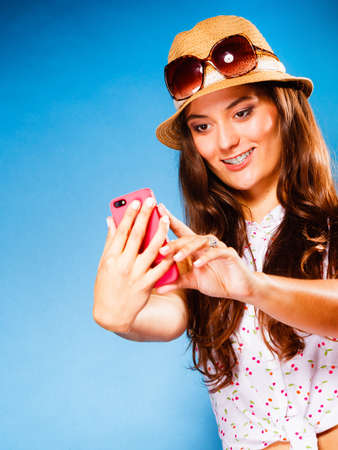 Technology and internet. Happy woman using cellphone texting on mobile phone. Teen girl reading sms on smartphone, taking selfie on blue photo
