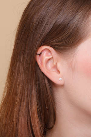 Closeup human female pierced ear with earrings Stock Photo