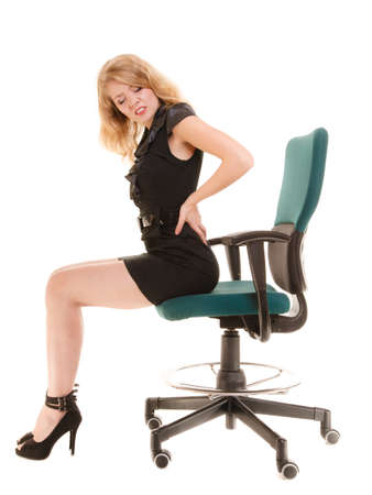Young businesswoman with backache. Blonde woman with back pain sitting on chair. Long working hours and health.  Business. photo