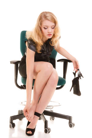 stoppage: Work stoppage and leg pain. Closeup of tired businesswoman woman sitting on chair and massaging feet isolated on white. Stock Photo