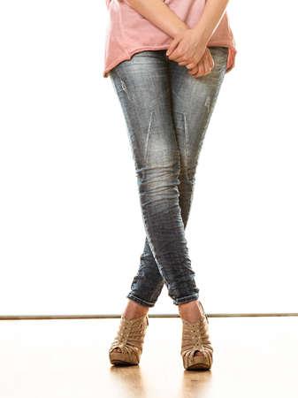 Moda y concepto de la gente. Piernas de la mujer en zapatos de tacón alto de la plataforma de mezclilla pantalones zapatos estilo casual aislado sobre fondo blanco Foto de archivo