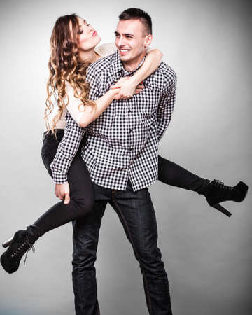 oncept: Love people and happiness oncept. Smiling young couple having fun, man giving piggyback ride to woman studio shot on gray