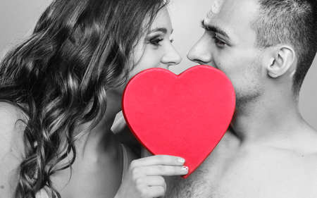 nacked: Attractive young couple kissing behind red heart against black & white photo